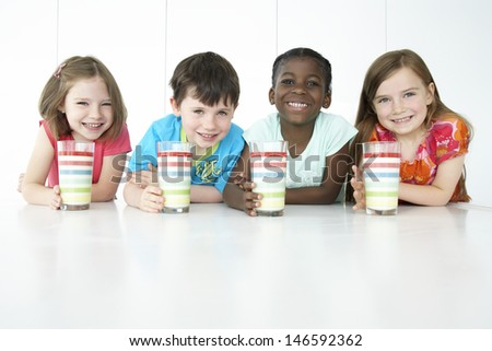 Portrait of smiling multiethnic boys and girls sitting at table with colorful glasses - stock photo