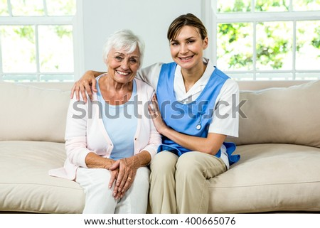 Portrait of smiling nurse with senior woman sitting on sofa at home - stock photo