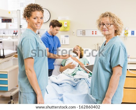 Portrait of smiling nurses standing against couple with newborn baby at hospital - stock photo