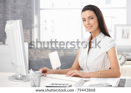 Portrait of smiling office girl sitting at desk, working on desktop computer. - stock photo