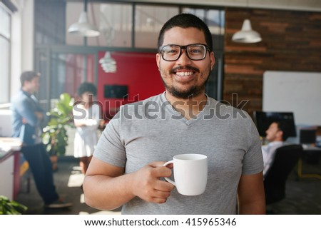 Portrait of smiling office worker having a coffee with his colleagues talking in the background. - stock photo