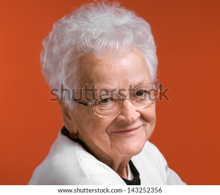 Portrait of smiling old woman on an orange background