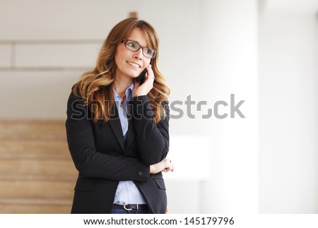 Portrait of smiling professional businesswoman on the phone in office  - stock photo