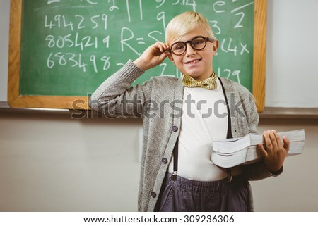 Portrait of smiling pupil dressed up as teacher holding books in a classroom - stock photo