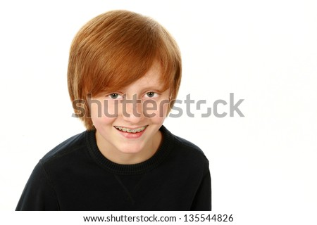 portrait of smiling redhead boy with braces isolated on white