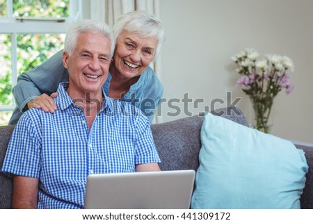 Portrait of smiling retired couple using laptop at home - stock photo