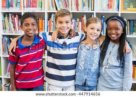 Portrait of smiling school kids standing with arm around in library at school