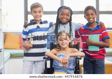 Portrait of smiling school kids standing with arm around in library at school - stock photo