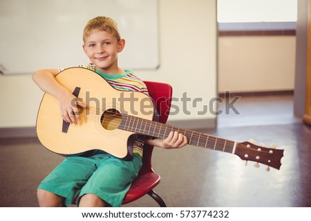 Portrait of smiling schoolboy playing guitar in classroom at school