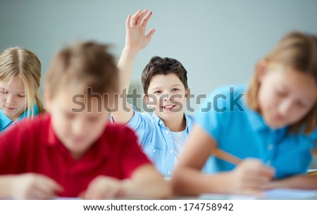 Portrait of smiling schoolboy raising hand at workplace with classmates near by - stock photo
