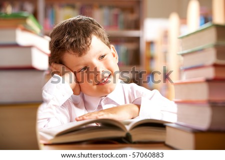 Portrait of smiling schoolboy sitting at the table with books on it - stock photo