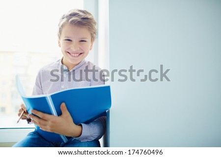 Portrait of smiling schoolboy with exercise-book looking at camera - stock photo