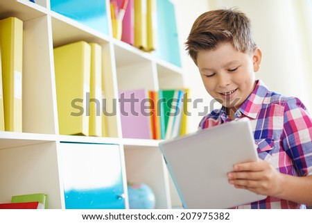 Portrait of smiling schoolboy working with touchpad