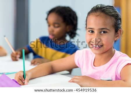 Portrait of smiling schoolgirl with classmate writing on book in classroom