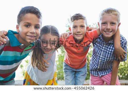 Portrait of smiling schoolkids standing with arms around in campus at school - stock photo