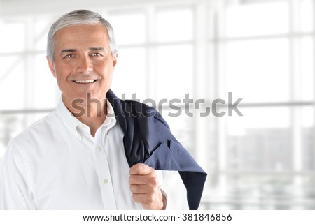 Portrait of smiling senior businessman standing against office window background while looking at camera, with his coat over his shoulder - stock photo