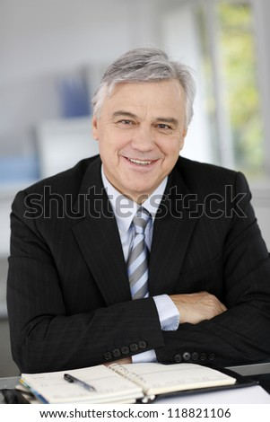 Portrait of smiling senior businessman with arms crossed - stock photo