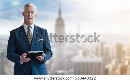 Portrait of smiling senior businessman with tablet