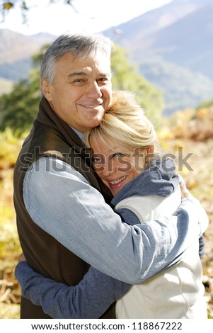 Portrait of smiling senior couple in countryside - stock photo
