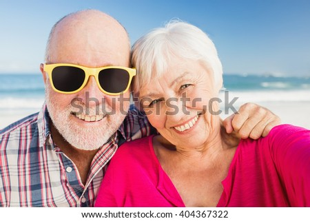 Portrait of smiling senior couple on the beach - stock photo