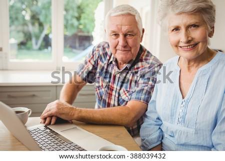 Portrait of smiling senior couple using laptop - stock photo