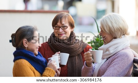 Portrait of smiling senior female friends drinking coffee at patio - stock photo