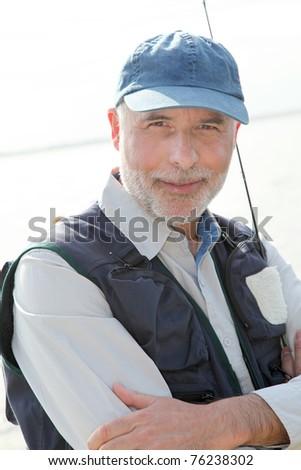 Portrait of smiling senior fisherman - stock photo