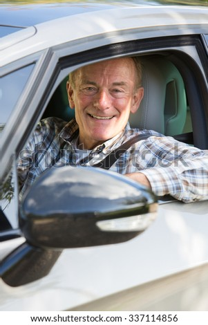 Portrait Of Smiling Senior Man Driving Car - stock photo