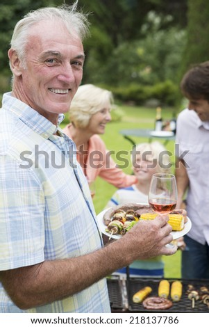 Portrait of smiling senior man holding plate of barbecue and wine - stock photo