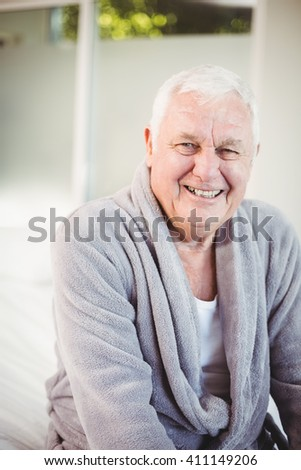 Portrait of smiling senior man in bedroom at home