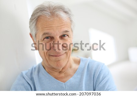 Portrait of smiling senior man with blue shirt - stock photo
