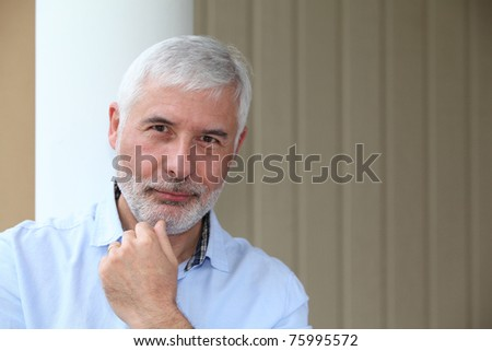Portrait of smiling senior man with hand on chin - stock photo