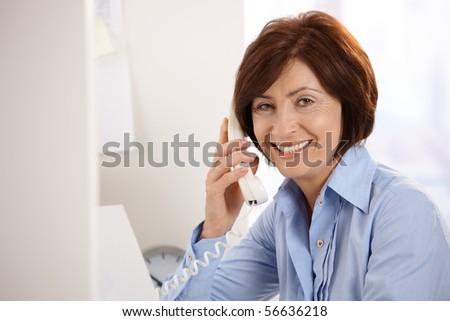 Portrait of smiling senior office worker sitting at desk, using landline phone, looking at camera. - stock photo