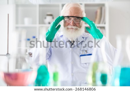 Portrait of smiling senior scientist wearing goggles and protective gloves