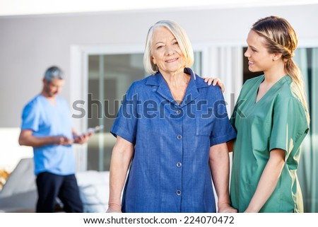 Portrait of smiling senior woman being assisted by female caretaker in nursing home - stock photo