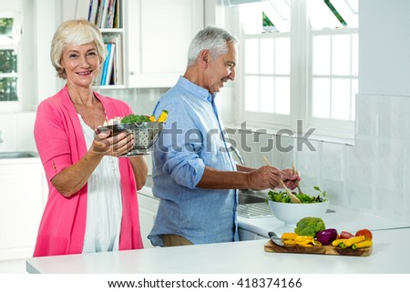 Portrait of smiling senior woman holding colander with man preparing vegetables in kitchen - stock photo