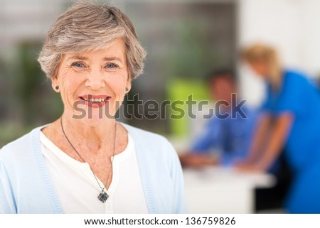 portrait of smiling senior woman in doctor's office - stock photo