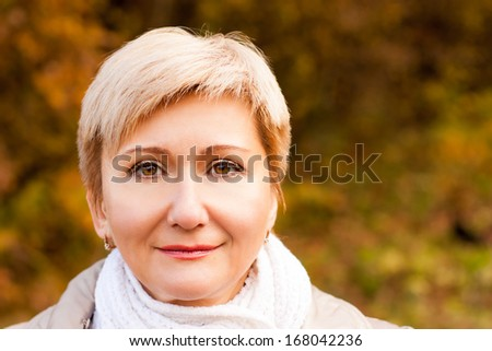 Portrait of Smiling Senior Woman on Autumn Background. Copy Space.