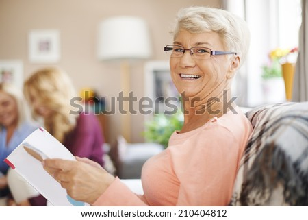 Portrait of smiling senior woman reading newspaper - stock photo