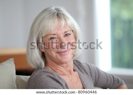 Portrait of smiling senior woman sitting in sofa - stock photo