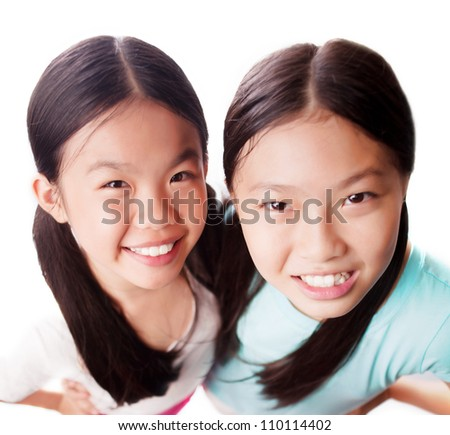 Portrait of smiling sisters looking at camera on white background
