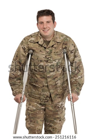 Portrait of smiling soldier with crutches against white background - stock photo