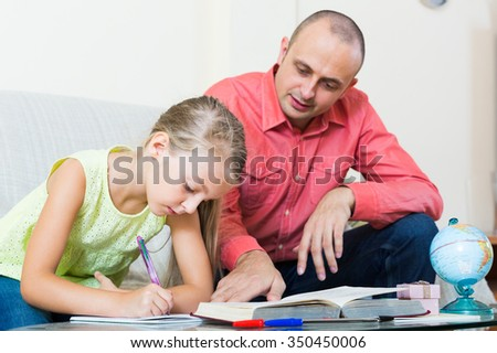 Portrait of smiling spanish dad helping schoolgirl to study at home.focus on girl