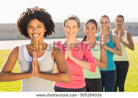 Portrait of smiling sporty women doing prayer position in yoga class in parkland - stock photo