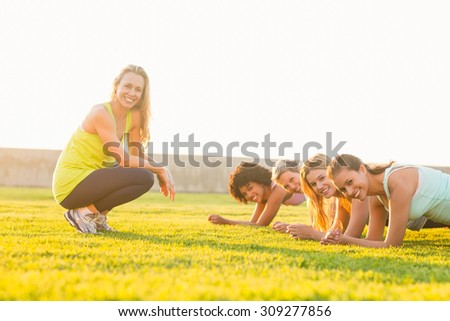 Portrait of smiling sporty women planking during fitness class in parkland - stock photo