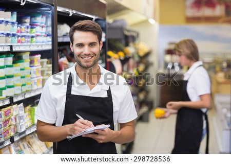 Portrait of smiling staff man writing on notepad at supermarket