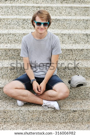 Portrait of smiling teenage boy sitting against grey background - stock photo