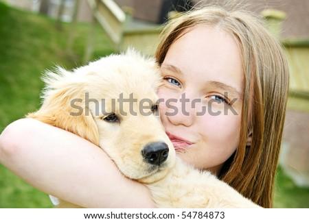 Portrait of smiling teenage girl holding golden retriever puppy - stock photo