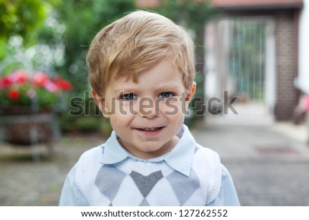 Portrait of smiling toddler boy on way to summer school kindergarten - stock photo