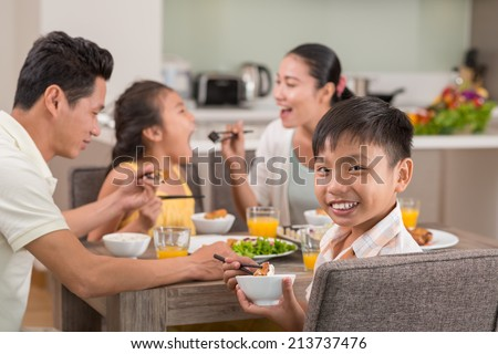 Portrait of smiling Vietnamese boy at the family dinner on the background of mother feeding his sister with sushi - stock photo